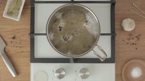 A pessoa põe a pimenta preta na água a ferver na bandeja do metal sobre a cozinha video estoque