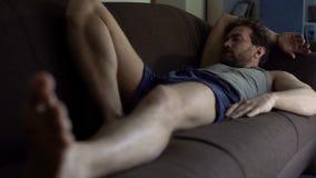 Pessoa preguiçosa no roupa interior que dorme no sofá após o dia útil duro, apatia, problemas foto de stock