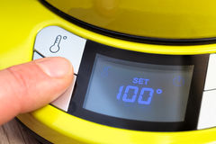 Pessoa que ajusta a temperatura elétrica da chaleira de chá a 100 C Fotos de Stock Royalty Free