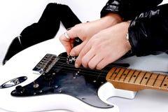Pessoa que ajusta uma guitarra de seu headstock sobre o fundo branco fotografia de stock