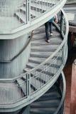 Pessoa que anda acima de uma escadaria espiral imagem de stock