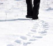 Pessoa que anda na neve e que deixa pegadas Imagem de Stock
