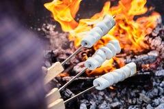 Pessoa que brinda marshmallows sobre um fogo do assado fotografia de stock royalty free