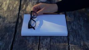Pessoa que coloca vidros de leitura em um livro branco vídeos de arquivo