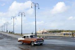 Pessoa que conduz seu carro do vintage no Malecon em Havana Imagem de Stock