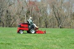 Pessoa que corta o gramado em uma segadeira de equitação Imagens de Stock