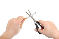 Pessoa que corta um close up do cigarro Fotografia de Stock