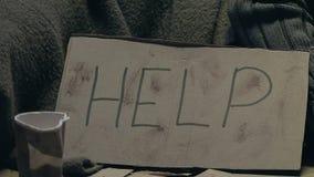 Pessoa que dá o dinheiro ao mendigo com sinal, piedade e doações da ajuda para pobres filme