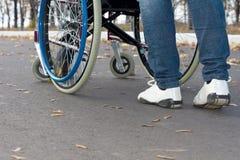 Pessoa que empurra uma cadeira de rodas Fotografia de Stock