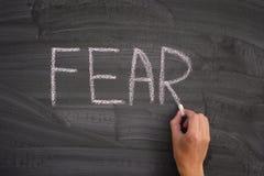 Pessoa que escreve o medo da palavra em um quadro-negro foto de stock