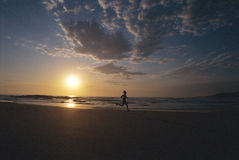 Pessoa que funciona ao longo da praia no por do sol Imagem de Stock Royalty Free