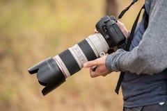 Pessoa que guarda a câmera de Canon com lente teleobjetiva fotos de stock