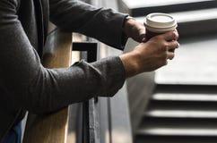 Pessoa que guarda o copo de café quente Imagens de Stock