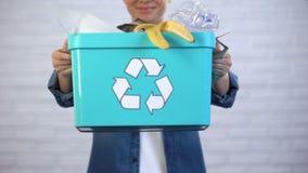Pessoa que guarda o escaninho de lixo com lixo descartável e plástico, classificação do desperdício video estoque