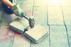 Pessoa que guarda o martelo e a quebra ao estilo do vintage do tijolo e ao s Imagens de Stock
