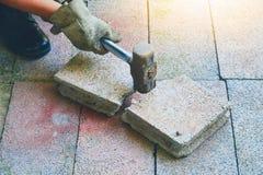 Pessoa que guarda o martelo e a quebra ao estilo do vintage do tijolo e ao s Fotos de Stock