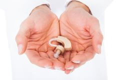 Pessoa que guarda a prótese auditiva nas mãos colocadas fotos de stock royalty free