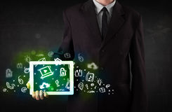 Pessoa que guarda a tabuleta com ícones e símbolos verdes dos meios Foto de Stock