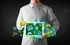 Pessoa que guarda a tabuleta com ícones e símbolos verdes dos meios Fotografia de Stock