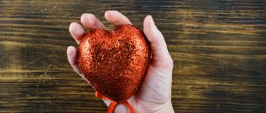 Pessoa que guarda um coração vermelho feito a mão em suas mãos Amor 14o fevereiro Dia do `s do Valentim Fotos de Stock Royalty Free