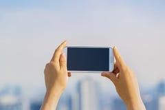 Pessoa que guarda um smartphone em um fundo da cidade Imagem de Stock
