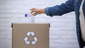 Pessoa que joga garrafas plásticas no escaninho de lixo, classificando o desperdício não-degradable vídeos de arquivo