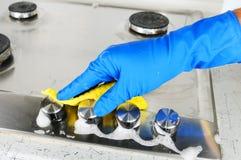 Pessoa que limpa um fogão de gás imagem de stock
