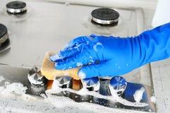 Pessoa que limpa um hob do fogão de gás imagens de stock