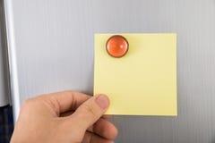 Pessoa que mantém a nota sticked na porta do refrigerador Foto de Stock Royalty Free