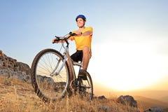Pessoa que monta uma bicicleta de montanha em um por do sol Foto de Stock