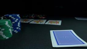 Pessoa que mostra sua plataforma no jogo de pôquer O jogador de cartão verifica sua mão, dois áss dentro, microplaquetas no fundo Fotos de Stock
