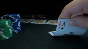 Pessoa que mostra sua plataforma no jogo de pôquer O jogador de cartão verifica sua mão, dois áss dentro, microplaquetas no fundo Imagem de Stock