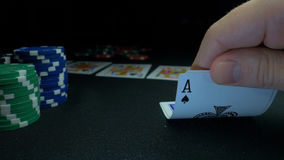 Pessoa que mostra sua plataforma no jogo de pôquer O jogador de cartão verifica sua mão, dois áss dentro, microplaquetas no fundo Fotografia de Stock