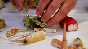 A pessoa que shucking ostras frescas com uma faca, came transporta-se à esquerda, close up vídeos de arquivo