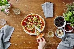 Pessoa que toma a primeira fatia fora da pizza deliciosa orgânica imagem de stock royalty free