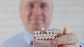 Pessoa que toma um sorriso de fumo da pausa e para oferecer um cigarro de um bloco novo filme