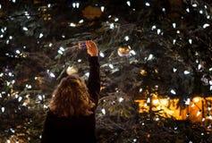 Pessoa que toma uma foto de uma árvore de Natal exterior grande na noite Imagem de Stock