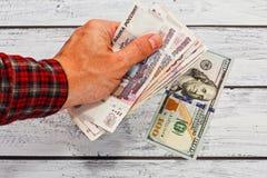 Pessoa que troca rublos de russo aos dólares americanos Imagens de Stock