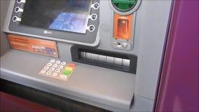 Pessoa que usa o caixa automático de máquina de dinheiro do atm video estoque