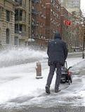 Pessoa que usa o snowblower após a tempestade de neve Fotos de Stock