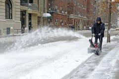 Pessoa que usa o snowblower após a tempestade de neve Fotografia de Stock