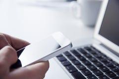 Pessoa que usa o telefone ao trabalhar em um portátil Fotos de Stock