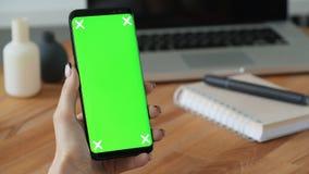 Pessoa que usa o telefone celular com visualização ótica verde à disposição filme