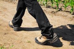 Pessoa que veste calças pretas e que caminha botas Foto de Stock Royalty Free