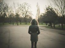 Pessoa que veste o revestimento morno que está no parque no por do sol Fotos de Stock