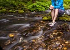 A pessoa senta-se na pedra coberta com o musgo no centro do fluxo rápido do rio, guardando seus pés na água clara Fotografia de Stock