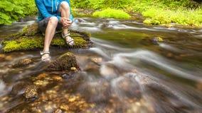 A pessoa senta-se na pedra coberta com o musgo no centro do fluxo rápido do rio, guardando seus pés na água clara Foto de Stock