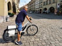 Pessoa superior com vidros de sol na bicicleta em Kramgasse Berna Foto de Stock Royalty Free