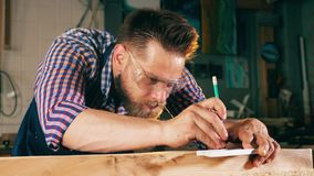 A pessoa trabalha com madeira, usando o lápis e uma régua Funcionamento idoso do carpinteiro vídeos de arquivo