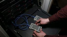 A pessoa trabalha com o verificador do LAN do cabo da rede vídeos de arquivo